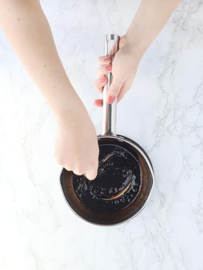 hand stirring molasses glaze in a small saucepan