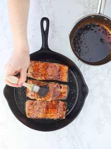hand brushing molasses glaze over salmon filets in a cast iron skillet