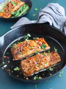 two glazed salmon filets garnished with parsley in a cast iron skillet