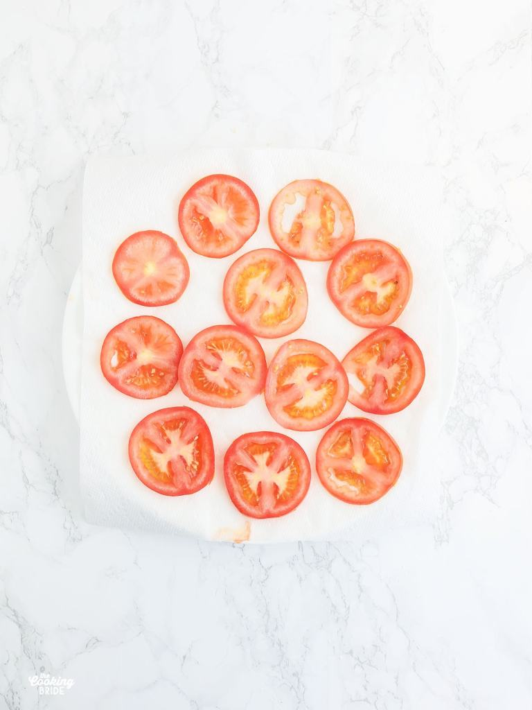 slices of fresh tomatoes drying on a layer of paper towels