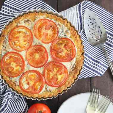 baked southern tomato pie on a dark wooden table with fresh tomatoes, plates and forks to the side