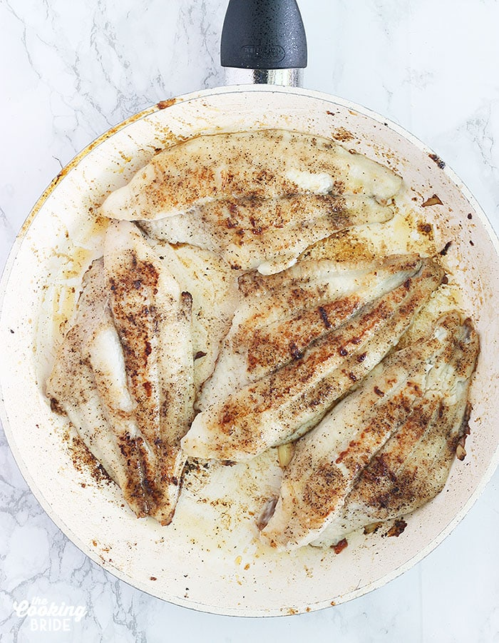 Sautéing seasoned catfish fillets in a skillet with olive oil