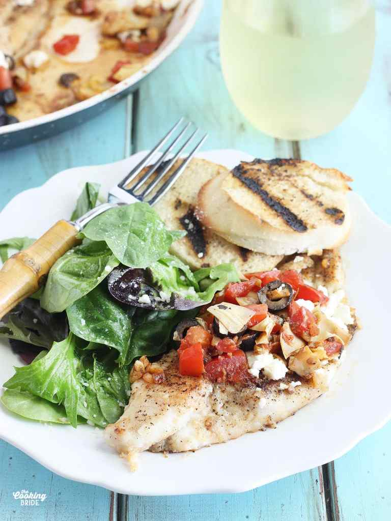 side view of Mediterranean Catfish fillets on a white plate with a fork and toasted bread to the side
