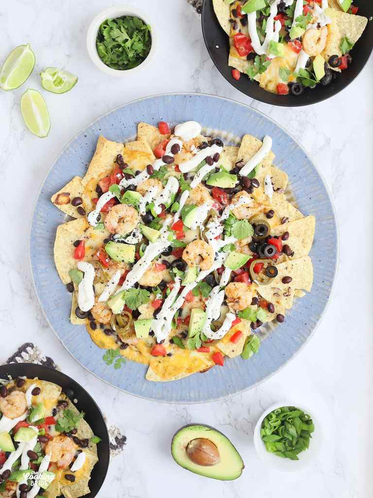 overhead shot of a large blue platter of shrimp nachos with to black bowls with individual servings of nachos to the side