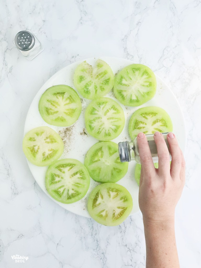 hand seasoning sliced green tomatoes with salt and pepper
