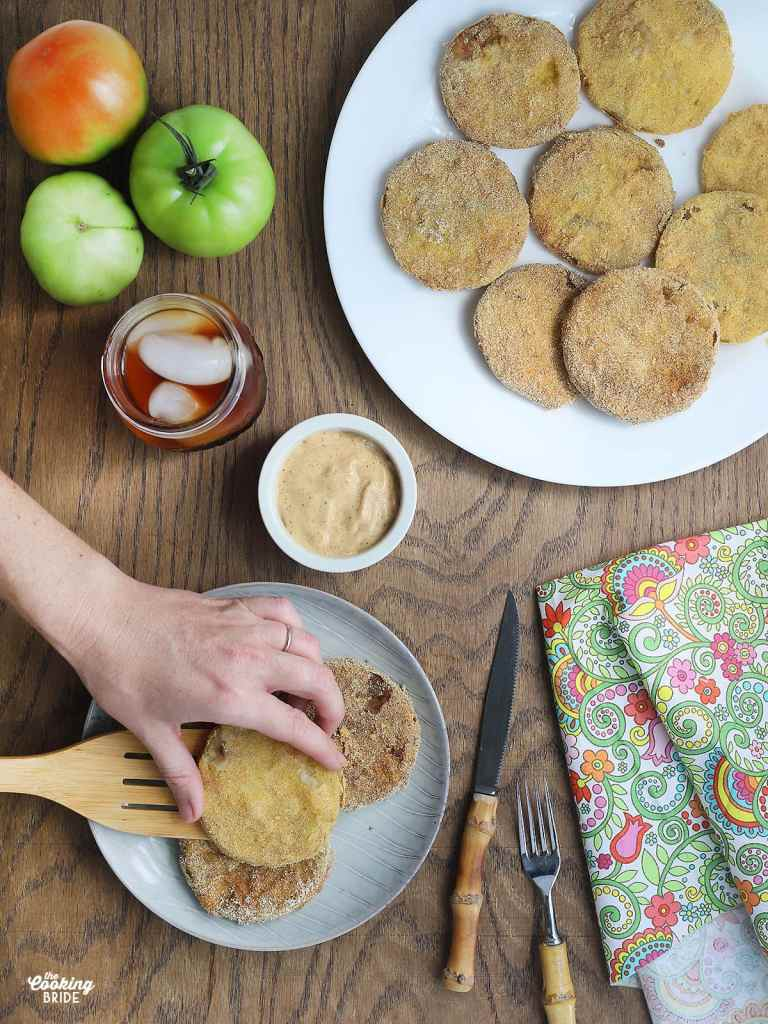 hand placing fried green tomatoes on a plate