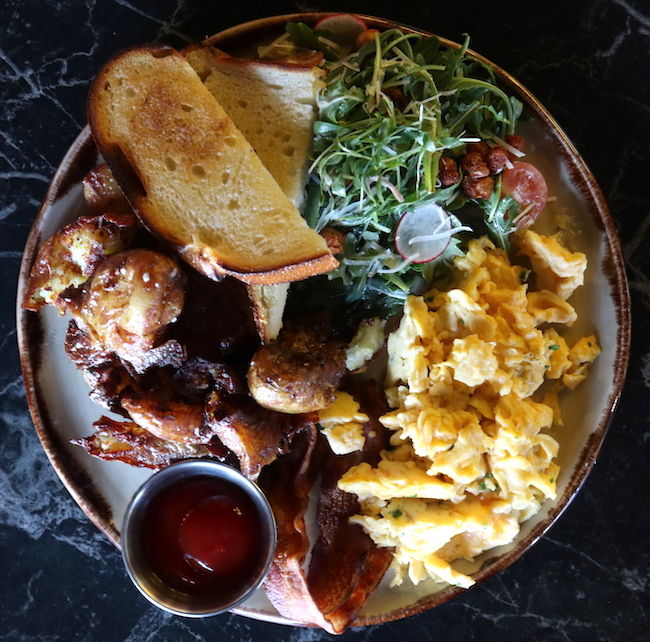 a plate of bacon, scrambled eggs, potatoes, salad and toast