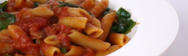 a dish of penne pasta with tomato sauce
