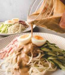 pouring dressing over sesame cold noodle.