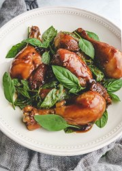 ooked three cup chicken drumsticks with basil in a white plate on top of gray cloth.