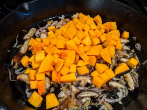butternut squash cubes, mushroom and shallot in a black skillet.