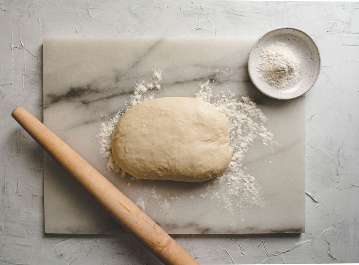 shaobing dough on a marble board with flour and rolling pin