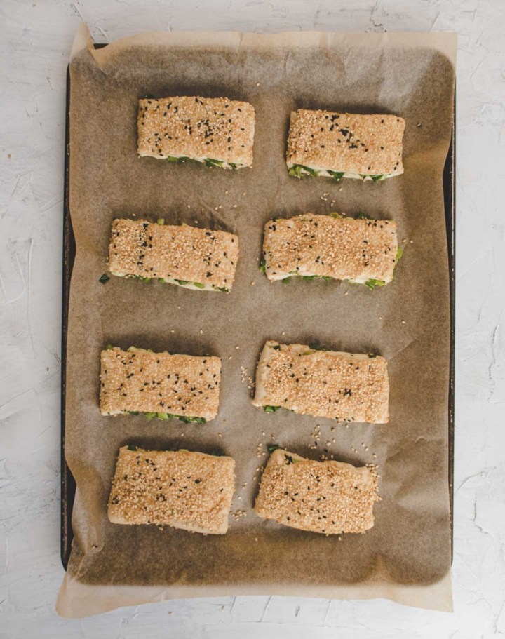 raw scallion shaobing on a backing sheet lined with a parchment paper