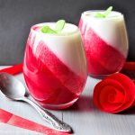 Easy strawberry desserts in glasses with red and white layers, served on grey table with a teaspoon and rose.