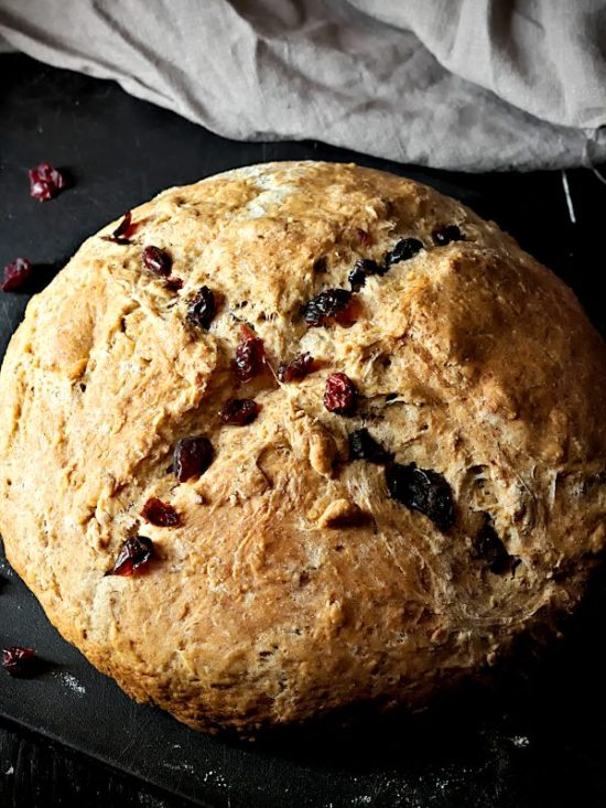 Irish soda bread with cross and cranberries on a black board.
