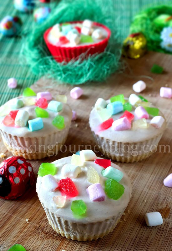 Easter desserts - mini cheesecakes with colorful marshmallows, served with Easter chocolate on a wooden board