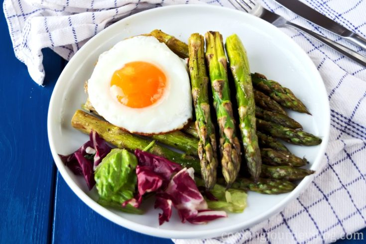 Roasted asparagus with egg, served on blue table