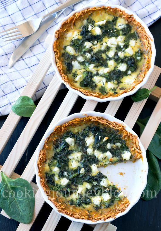 Spinach Quiche Recipe - How To Make Quiche. Spinach quiche, served on wooden board on the black table. One slice is missing.