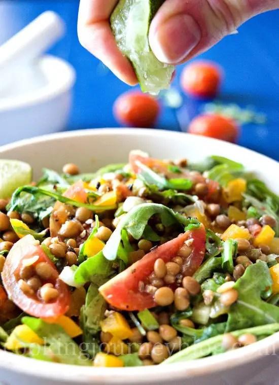 Squeezing lime juice on lentil salad