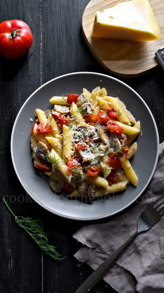 Creamy Mushroom Pasta with Tomatoes, cheese and dill, served on gray plate