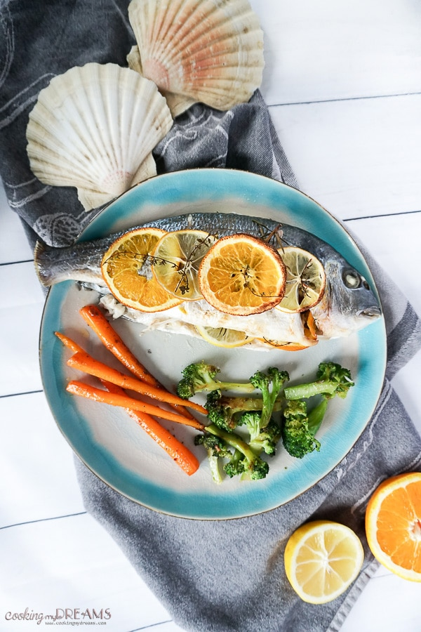 Overhead photo of cooked sea bream with citrus slices and a side of vegetables