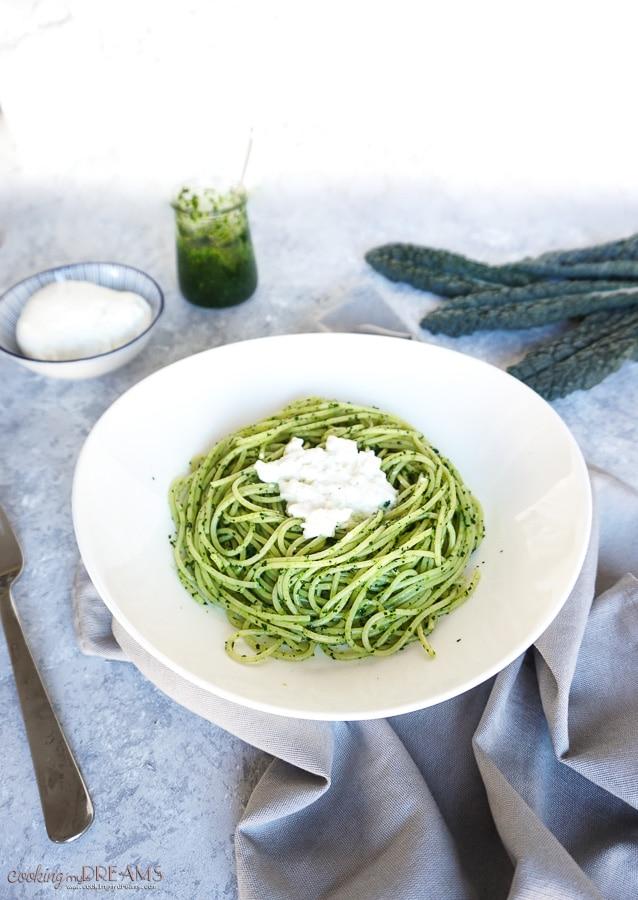 white plate with spaghetti and tuscan kale pesto with burrata