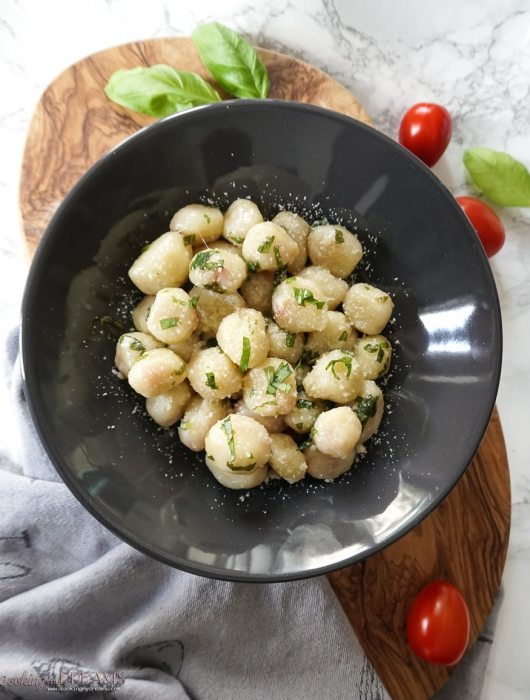 overhead photo of black plate with potato gnocchi