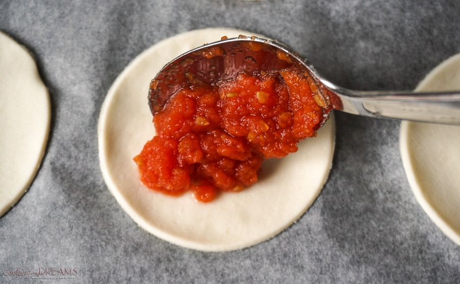 spoon dropping tomato sauce on circle dough