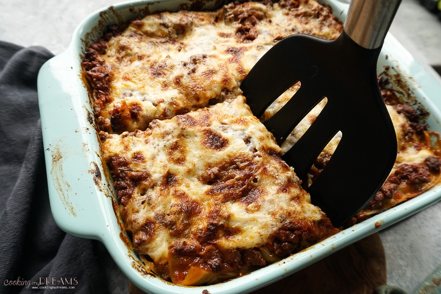 spatula cutting a portion of italian lasagna from the pan