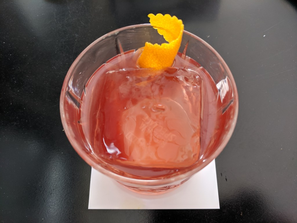 The malbaroni cocktail with an orange peel garnish
