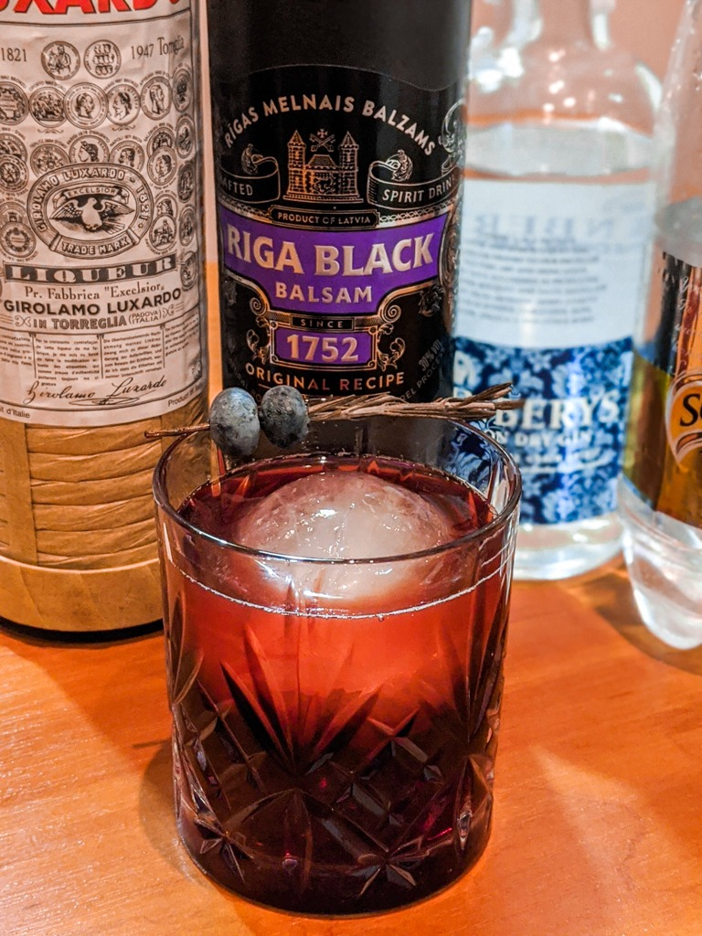 The Black Latvian Cocktail with ingredients behind it