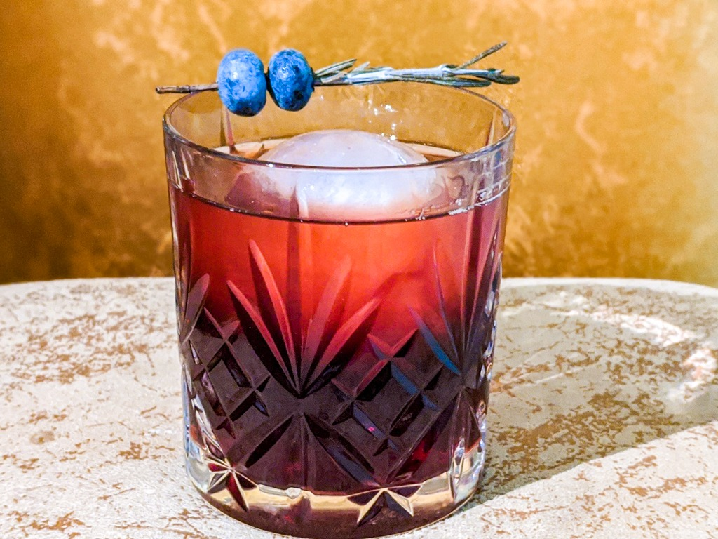 The Black Latvian Cocktail with a garnish of rosemary and blueberry