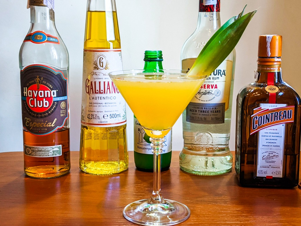 The Yellow bird cocktail with bottles in the background