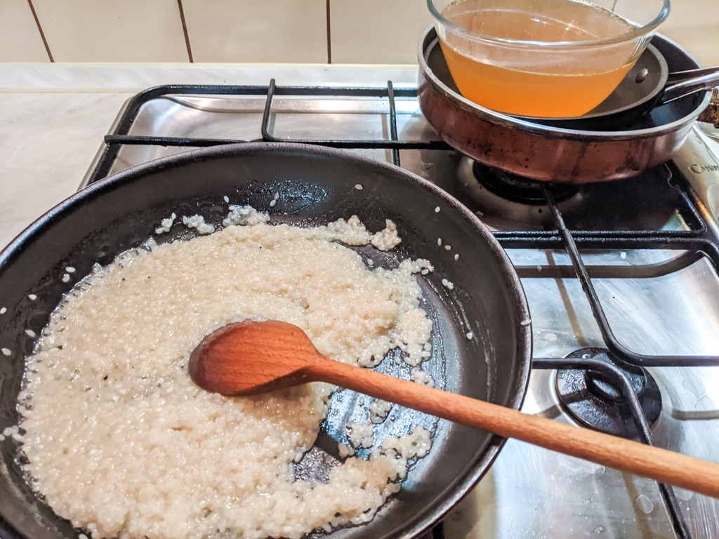 Stirring the risotto and adding chicken stock