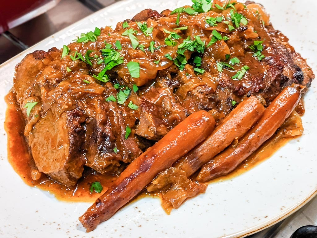 Onion Braised Beef Brisket on a serving dish with carrots and parsley