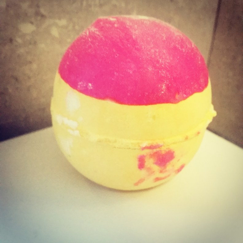 The whole pink and yellow bath bomb before going into the water. The pink is messily splobbed around and over the yellow.