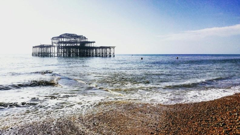 The burned down Brighton pier stands in the sea on one of the first sunnier days signaling the end of winter