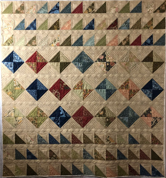 Half square triangle quilt with detailed cross hatch quilting