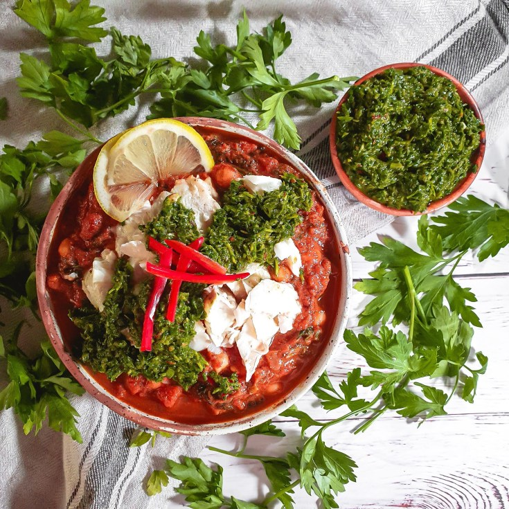 A spicy chickpea stew served with fresh and zesty chermoula, and lemon baked cod recipe. A quick and easy dinner recipe idea with vegetarian vegetable stew and baked cod with Morrocan influnces. #recipe #recipes #seafood #fish #stew #tagine #vegetarian #healthy #midweekmeal
