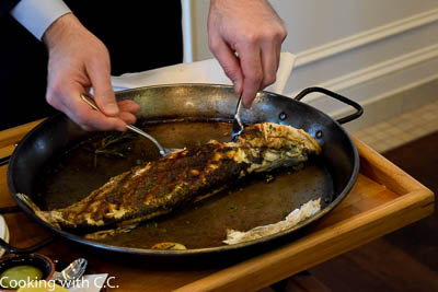 Starting With The Cut Edge Of The Fish, Pulling Out The Herbs And Lemons