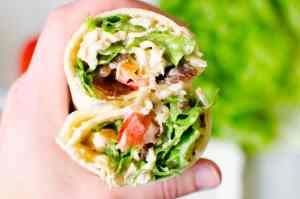 A great healthy lunch option is this BLT Chicken Wrap loaded with lettuce, bacon, tomatoes, and chicken.