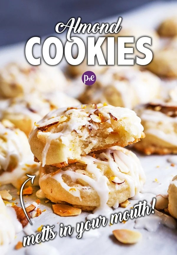 These Almond Cookies are melt-in-your-mouth delicious and super easy to make! The cookies have a chewy texture with crunchy bits of almond. They are topped with an almond glaze and a touch of orange zest that will leave you wanting more (and more and more)! #almondcookie #christmascookie #cookie #recipe