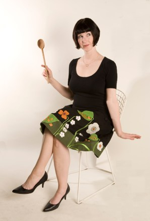 Photo of Jennifer Robbins seated in a chair holding a wooden spoon