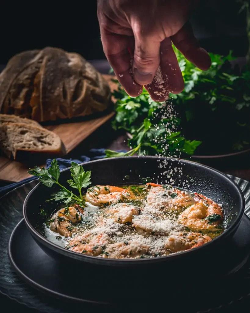 Parmesan sprinkled on top of shrimp scampi