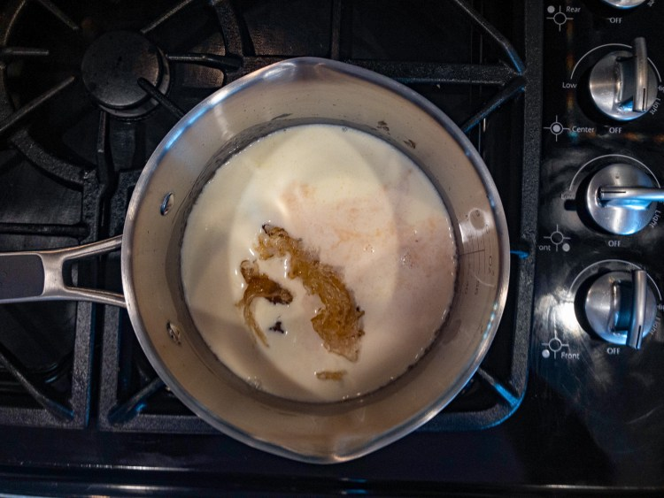 caramel, heavy cream, vanilla extract, and salt cooking on the stove-top in a stainless steel saucepan with pour spouts on lowest heat setting