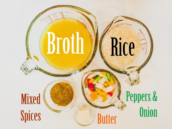 ingredients in glass measuring cups and clear bowls, including rice, broth, butter, mixed spices, and green, red, orange, and yellow peppers and onions