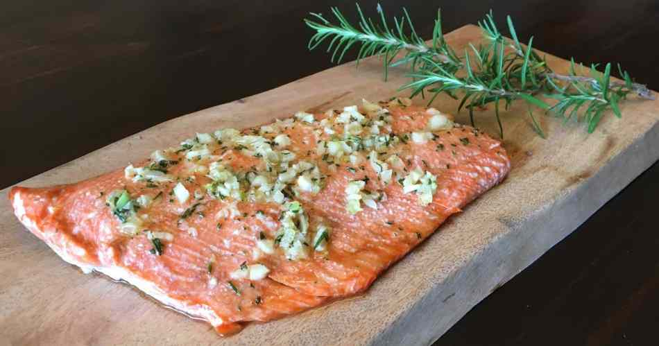 Baked Wild Salmon on wooden board with rosemary sprig