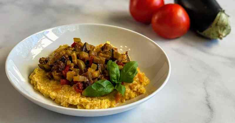Caponata over polenta with sprig of basil