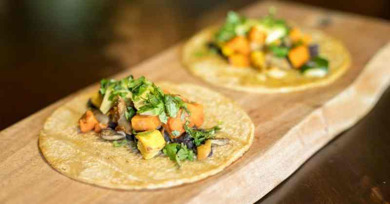 photo of two roasted veggie and black bean tacos on corn tortillas