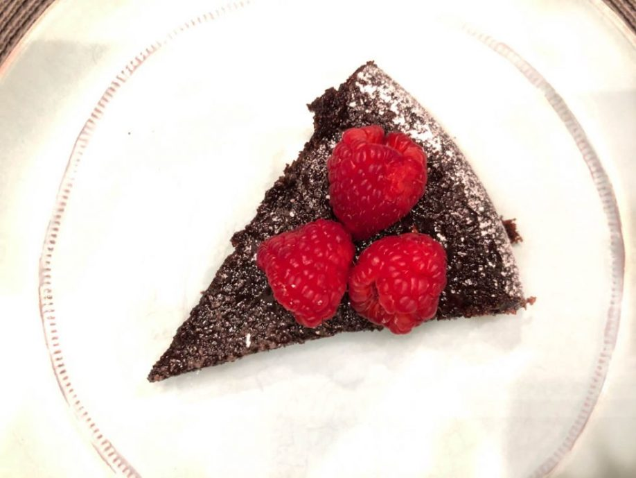 Slice of Dark Chocolate Olive Oil Cake on a plate with raspberries